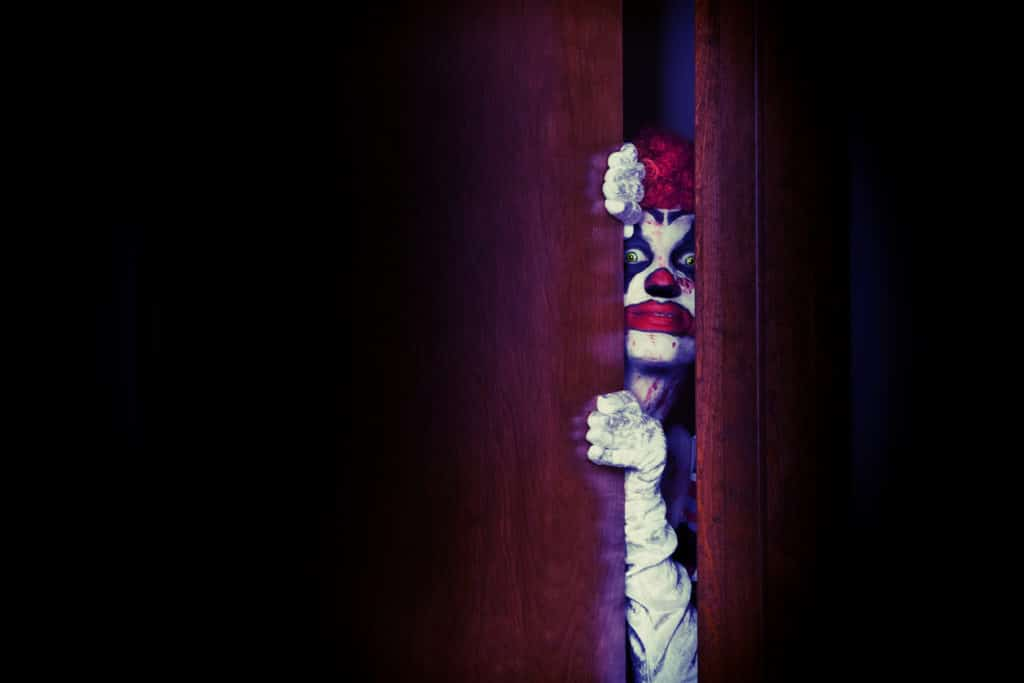 creepy clown peeking out of closet photo